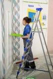 De vrouwelijke schilder verfraait muur, uitvoerend taak royalty-vrije stock foto