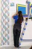 De vrouwelijke schilder verfraait muur, uitvoerend taak royalty-vrije stock foto's
