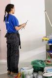 De vrouwelijke schilder verfraait muur, uitvoerend taak stock afbeelding