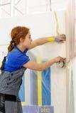 De vrouwelijke schilder verfraait muur, uitvoerend taak stock fotografie