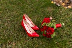 De vrouwelijke schoenen van het manier rode huwelijk met bruid` s boeket van rode rozen en groene bessen op groene grasachtergron Stock Afbeeldingen