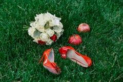 De vrouwelijke schoenen van het manier rode huwelijk met bruid` s boeket van witte rozen en twee rode granaten op groene grasacht Royalty-vrije Stock Foto