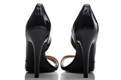 De vrouwelijke schoenen van het octrooileer op een witte achtergrond Stock Foto's