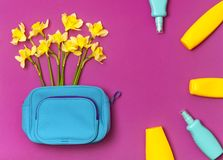 De vrouwelijke schoonheidsmiddelenzak, cosmetischee producten, zonneschermroom, nevel, gele narcissengele narcis bloeit op helder royalty-vrije stock foto's