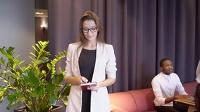 De vrouwelijke secretaresse begroet de onderneemster op de onderhandelingen met haar werkgever in de koffie stock videobeelden