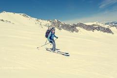 De vrouwelijke skiër die van het achter-land een steile helling aanpakken stock afbeelding