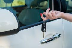 De vrouwelijke sleutel van de holdingsauto stock afbeeldingen