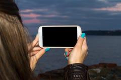 De vrouwelijke Slimme Telefoon van de Handholding op Avond Stock Fotografie