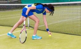 De vrouwelijke speler neemt een tennisbal op een hof op Stock Foto's