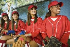 De vrouwelijke Spelers die van het Honkbal in een Rij zitten royalty-vrije stock afbeeldingen