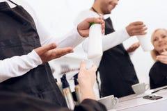 De vrouwelijke stilist toont duimen tot rijpe vrouw De kapper adviseert haarshampoo voor vrouw stock foto