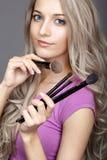 De vrouwelijke stilist van de blondeschoonheid - visagist met make-upborstels stock foto