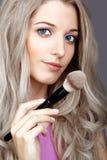 De vrouwelijke stilist van de blondeschoonheid - visagist met make-upborstels royalty-vrije stock foto's