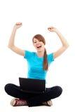 De vrouwelijke student heft wapens op zittend met laptop Royalty-vrije Stock Afbeeldingen