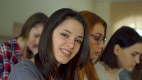 De vrouwelijke student raakt haar haar bij de lezingszaal royalty-vrije stock foto