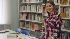 De vrouwelijke student stelt bij de bibliotheek royalty-vrije stock afbeeldingen