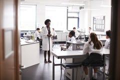 De vrouwelijke Studenten die van Teaching High School van de Middelbare schoolprivé-leraar Uniformen in Wetenschapsklasse dragen stock fotografie