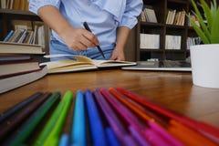 De vrouwelijke studentenlezing boekt studieonderzoek naar bibliotheek voor onderwijsconcept stock foto