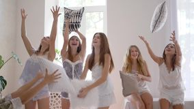 De vrouwelijke studentenpartij, gelukkige gezonde meisjes in pyjama'spret werpt hoofdkussens binnen in lucht stock videobeelden
