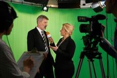 De vrouwelijke Studio van Presentatorinterviewing in television met binnen Bemanning stock fotografie