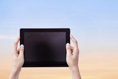 De vrouwelijke Tablet van Handenhoding met Bueatiful-zonsonderganghemel stock foto