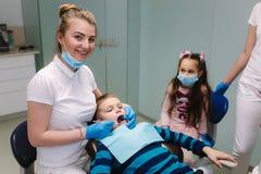 De vrouwelijke tandarts van de meisjehulp, nieuwe tanden examinationand behandeling van holten stock afbeelding