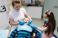 De vrouwelijke tandarts van de meisjehulp, nieuwe tanden examinationand behandeling van holten royalty-vrije stock foto