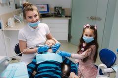 De vrouwelijke tandarts van de meisjehulp, nieuwe tanden examinationand behandeling van holten royalty-vrije stock foto's