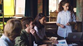 De vrouwelijke teamleider spreekt aan haar multi-etnisch team die bedrijfsstrategie in bureau van internationaal bedrijf bespreke stock footage