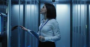 De vrouwelijke technicuswerken aangaande een tablet in een datacentrum stock video