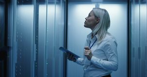 De vrouwelijke technicuswerken aangaande een tablet in een datacentrum stock videobeelden
