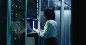 De vrouwelijke technicuswerken aangaande laptop in een datacentrum stock video