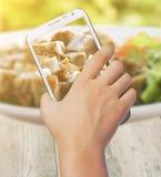 De vrouwelijke telefoon van de handholding tegen dichte omhooggaand op Gebraden gesneden varkensvlees Royalty-vrije Stock Foto's