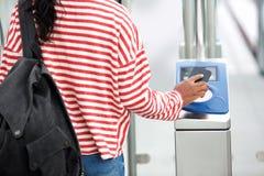 De vrouwelijke telefoon van de handholding aan open turnstile stock afbeelding
