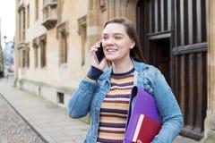 De vrouwelijke Telefoon van Studententalking on mobile buiten de Universiteitsbouw stock foto's