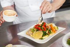De vrouwelijke Teller van Chef-kokgarnishing dish at Stock Afbeelding