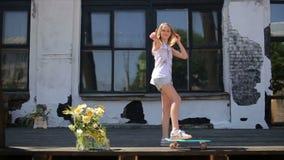 De vrouwelijke tiener op skateboard bekijkt de camera stock videobeelden