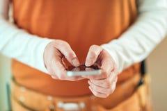 De vrouwelijke timmerman gebruikt mobiele telefoon voor tekstberichten stock afbeelding
