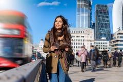 De vrouwelijke toerist die van Londen onderaan de Brug van Londen op een sightseeingsreis lopen stock fotografie