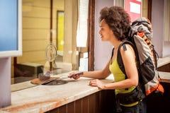 De vrouwelijke toerist koopt een kaartje bij de eindteller van het postkaartje stock fotografie