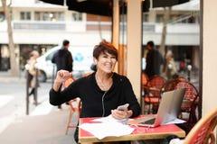de vrouwelijke toerist op middelbare leeftijd luistert muziek door smartphone en danci royalty-vrije stock foto's