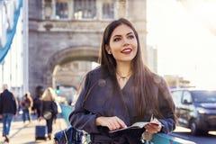 De vrouwelijke toerist van Londen met een reisgids in haar dient het UK in royalty-vrije stock foto