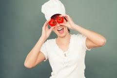 De vrouwelijke tomaten van de kokholding op haar ogen stock afbeeldingen
