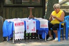 De vrouwelijke verkoper zit en haakt rushnyks voor verkoop in Nesvizh Stock Afbeelding