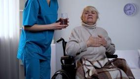 De vrouwelijke verpleegster die pillen en oud waterglas geven legt het lijden van borst aan pijn, geneeskunde stock foto