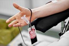 De vrouwelijke verpleegster trekt het bloed van de donor van container in flesjes Royalty-vrije Stock Foto's