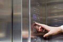 De vrouwelijke vinger drukt de knoop voor de lift stock fotografie