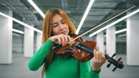 De vrouwelijke vioolspeler presteert in een lege ruimte stock videobeelden