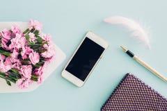 De vrouwelijke vlakte legt op blauwe achtergrond, hoogste mening van vrouwen` s Desktop met envelop, bloemen, pen, blocnote en sm Stock Foto's