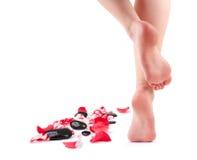 De vrouwelijke voeten en stenen van het Kuuroord met roze bloemblaadjes Royalty-vrije Stock Foto's